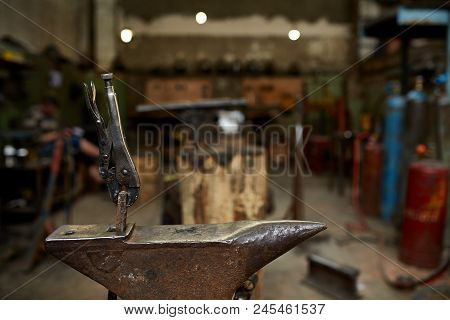 Big heavy anvil and pliers in the blacksmith's workshop, close-up, selective focus. Workshop background. Blurred background. Nesessary equipment for succesful manufacturing. Craftsman tools. Labour equipment. Art and crafts concept. poster
