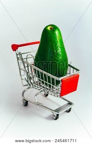 Shopping trolley with a fresh green avocado. Fruit consumption concept, pushcart on wheels. poster