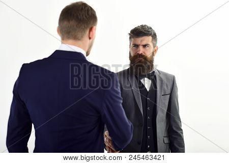 Businessmen, Business Partners Meeting, White Background. Business Partners On Serious Faces Handsha