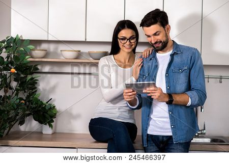 Modern Device. Cheerful Young Couple Resting Together In The Kitchen While Using Their Laptop