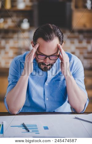 Portrait Of Tired Businessman With Migraine After Work At Home Office