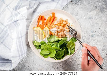 Modern Vegan Food, Person Eat  Savory Yogurt Bowl With Beans, Chickpeas, Spinach, Spicy Carrots, Lem