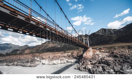 Wide-angle Panoramic Shot Of The Pendant Bridge Over The River In Mountain Settings With Cliffy Wate