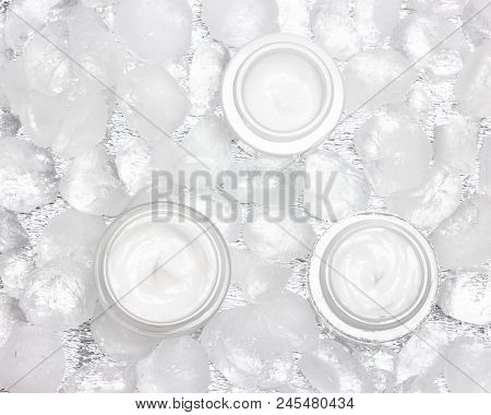 Cooling Effect Face Skincare Products. Glass Jars Of Moisturizing Cream Surrounded By Ice Cubes. Top