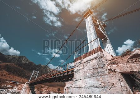 Close-up Wide-angle Shot Of The Suspension Bridge With Concrete Foundation Over The River In Mountai