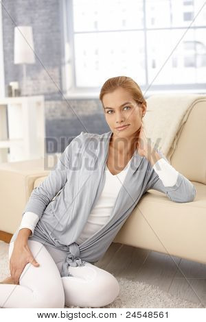 Portrait of pretty woman sitting on floor, posing in front of sofa in living room, smiling at camera.?