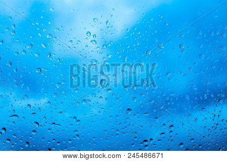 Drops Of Rain On Blue Glass Background. The Sky With Clouds On Background.