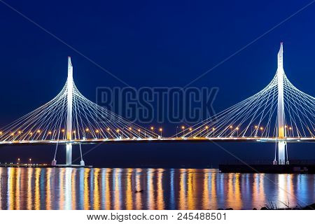 Cable-stayed bridge connects the roads of Western high-speed diameter in St. Petersburg, Russia. Night lighting of bridge is reflected in water of Peter's fairway. Modern industrial road structures poster