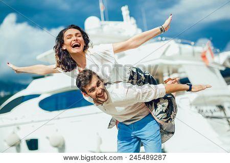 Young Beautiful Tourist Couple Enjoying Summer Holiday On The Seaside. Joyful Girl Piggybacking On Y