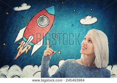 Portrait Of Smiling Student Girl Pointing Her Finger Up, Showing A Drawn Rocket Ship Take Off In Spa
