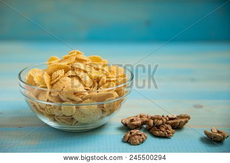 Tasty Cornflakes With Walnut In Glass Bowl On Blue Background.