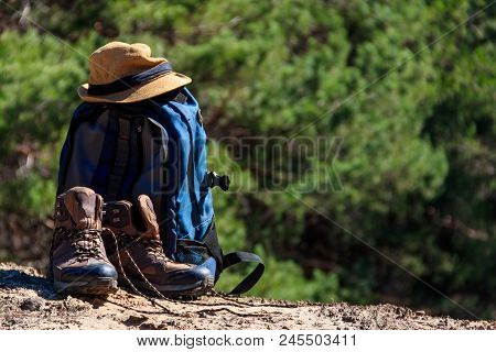 Tourist Backpack, Hiking Boots And Hat On The Glade In Pine Forest