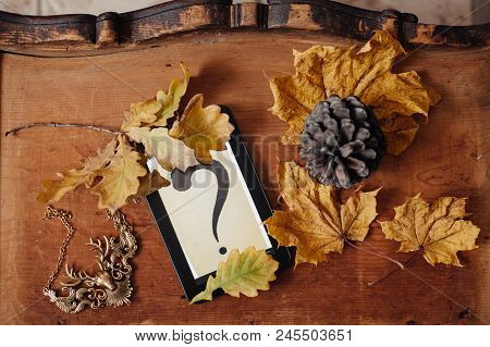 Autumn Leaves And A Question Mark Symbol In Ebook On A Wooden Background