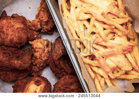 Flat Lay Above Table With Fried Chicken Wings And French Fries In The Box. Served Unhealthy Meal. Fa