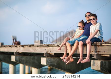 Happy beautiful family of father and kids outdoors on wooden jetty during summer vacation at luxury resort