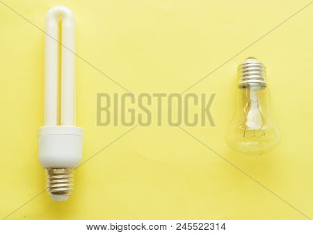 Energy-saving Lamp Vs. Incandescent Lamp . The Concept Of Energy Saving . On A Yellow Background.the