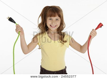 Waist up front view of female child holding two electrical cords, on white background.