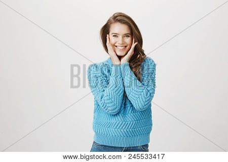 Pleasant Charming Woman With Beautiful Face Holding Hands On Cheeks And Smiling Broadly As If Being