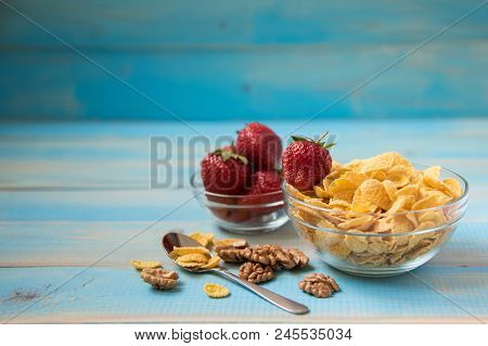 Tasty Cornflakes With Walnut And Strawberries In Glass Bowl On Blue Background. Corn Flakes, Copy Sp