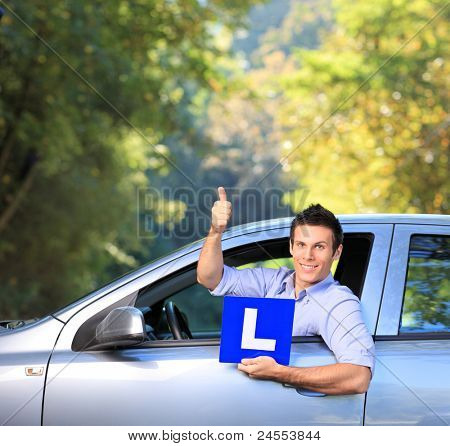 Happy male in his car holding a  L sign and giving thumb up after having his driver's licence
