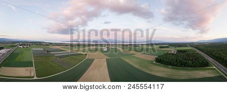 Aerial panorama image of green agricultural fields with Mont Blanc and Lake in background
