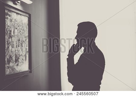 Man In Gallery Room Looking At Picture. Black And White