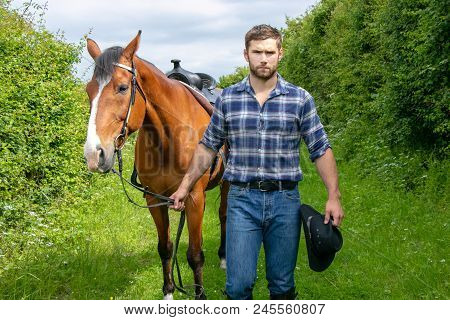 Good Looking, Hunky Cowboy With Boots, Chequered Shirt And Hat Walks In Front Of His Stallion, Horse