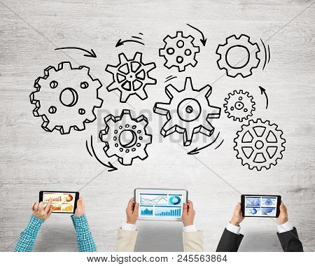 Group Of Three People With Devices In Hands Working Together As Symbol Of Networking And Communicati
