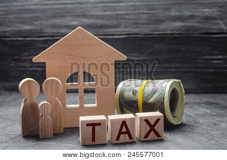 Wooden Figures Of The Family Stand Near A Wooden House And Money. Property Tax. Payment Of Taxes To
