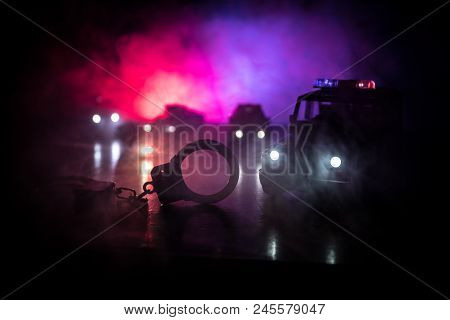 Police raid at night and you are under arrest concept. Silhouette of handcuffs with police car on backside. Image with the flashing red and blue police lights at foggy background. Slider shot poster