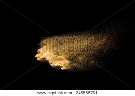 Golden Sand Explosion Isolated On Black Background. Abstract Sand Cloud. Golden Colored Sand Splash