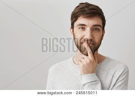 How About Going On Trip Together. Studio Shot Of Curious Thinking Caucasian Bearded Guy, Squinting A