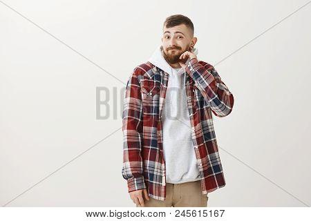 Portrait Of Emotive Joyful European Boyfriend With Beard And Trendy Haircut, Touching Neck And Smili