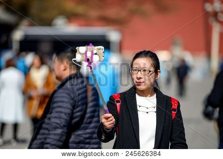 Beijing, China - March 11, 2016: Forbidden City. Tourists Photograph Selfie On The Background Of The