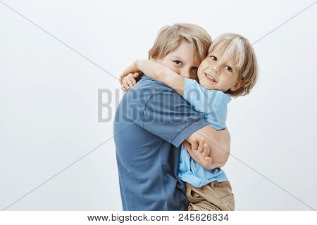 Brothers Are Best Friends. Portrait Of Cute European Boy Hugging Brother And Gazing At Camera, Being