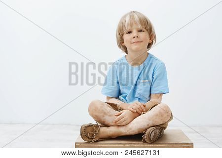 Indoor Shot Of Cute Happy Blond Child With Positive Smile Sitting With Crossed Hands, Having Vitilig