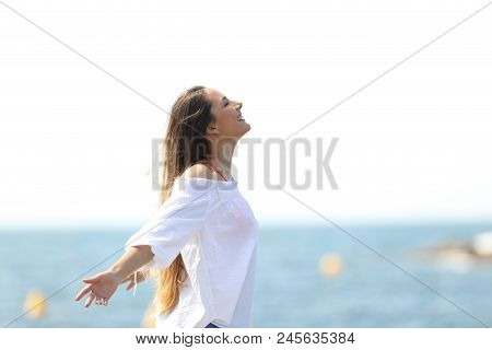 Side View Portrait Of A Relaxed Woman Breathing Fresh Air On The Beach