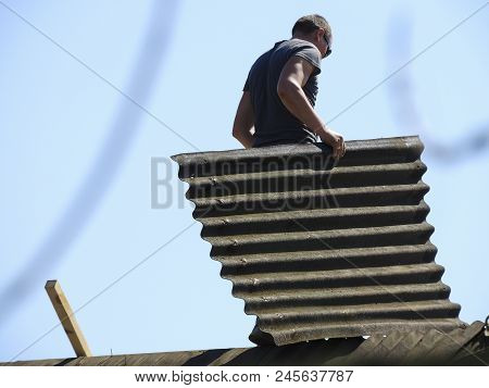 The Roofer Carries Slate On The Roof. Roof Dismantling