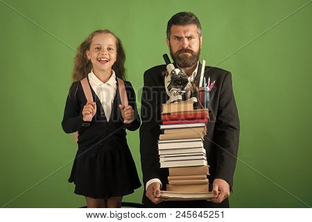 Home Schooling And Back To School Concept Kid And Dad Hold Pile Of Books With School Supplies. Girl