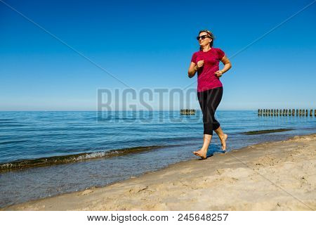 Middle-aged woman running on beach