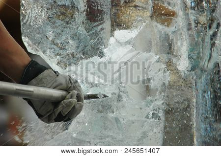A Man Is Carving A Block Of Ice Into A Statue. Only His Arm Can Be Seen. He Is Using An Ice-pick. Sh