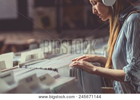 Young attractive girl browsing records in the store
