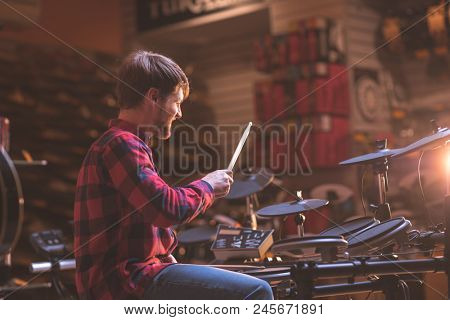 Young musician playing drums in a music store
