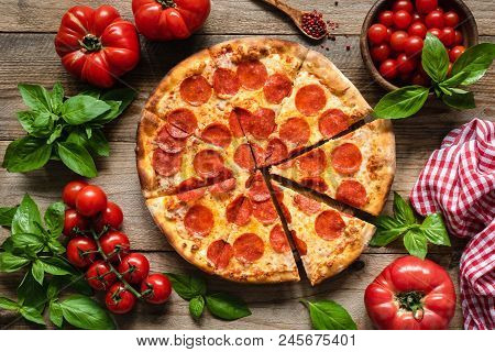 Pepperoni Pizza, Tomatoes And Basil. Tasty Pepperoni Pizza On Rustic Wooden Background. Overhead Vie