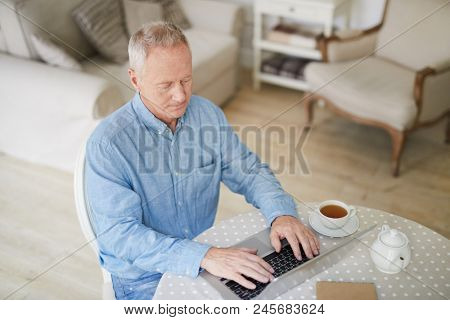 Serious mature man with laptop sitting by table in the kitchen, having tea and browsing in the net