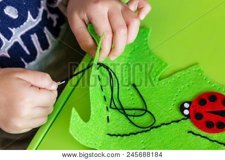 Child Making Felt Soft Toy Of Green Leaf And Red Ladybag . Child Diy Activity. Close-up. Children Ha