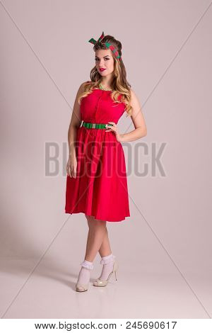 Pretty Girl In Red Dress With Hairdo Stands In Grey Studio, Pin Up Style