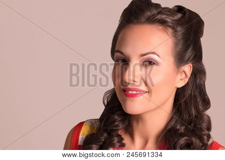 Pretty Brunette With Hairdo And Make Up Smiles In Studio, Pin-up Style, Close-up Portrait