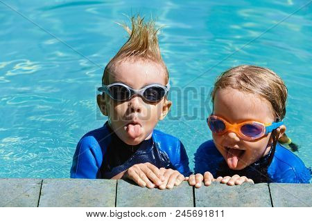Happy Children In Wetsuits And Goggles Learn To Swim, Have Fun At Poolside In Outdoor Pool. Healthy