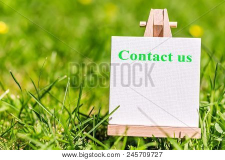 Contact Us Communication Concept. Sign Plate With Words Contact Us In The Green Grass Nature Meadow